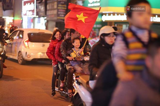 """Nhiều gia đình cùng nhau ra đường ăn mừng chiến thắng của ĐT Việt Nam. Tuy nhiên, vẫn có những hình ảnh không mấy đẹp mắt khi nhiều người """"quên"""" không đội mũ bảo hiểm. Ảnh: Việt Anh."""