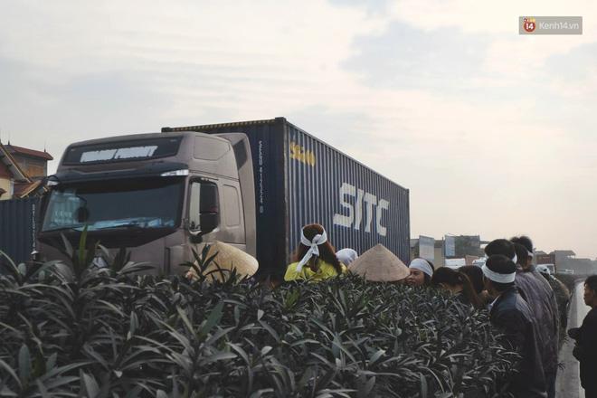 Đoàn xe tang ngược chiều xe container, nhiều người phải nép sát mép đường chờ dòng phương tiện đi qua mới tiếp tục di chuyển.