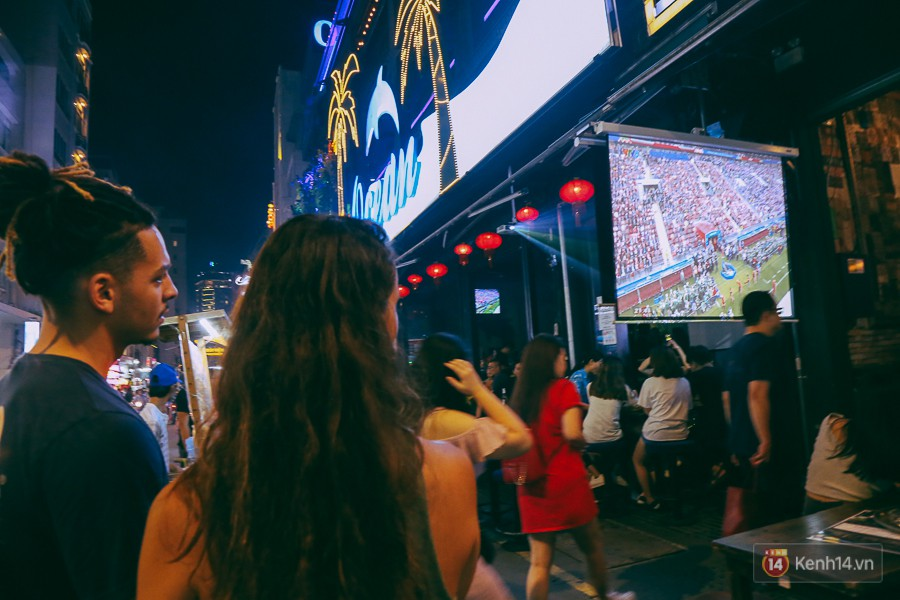 Hai du khách chăm chú theo dõi lễ khai mạc World Cup.