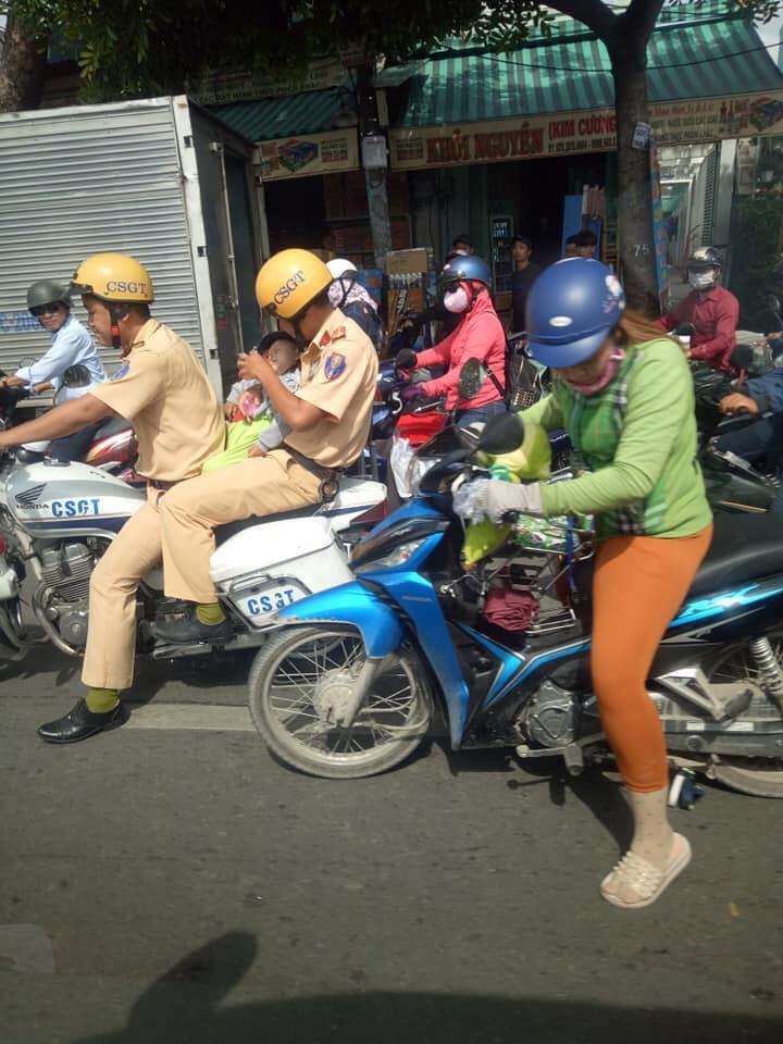 2 đồng chí CSGT giúp đỡ đưa cháu bé đến bệnh viện khi đang tắc đường. Ảnh: Quang Chánh