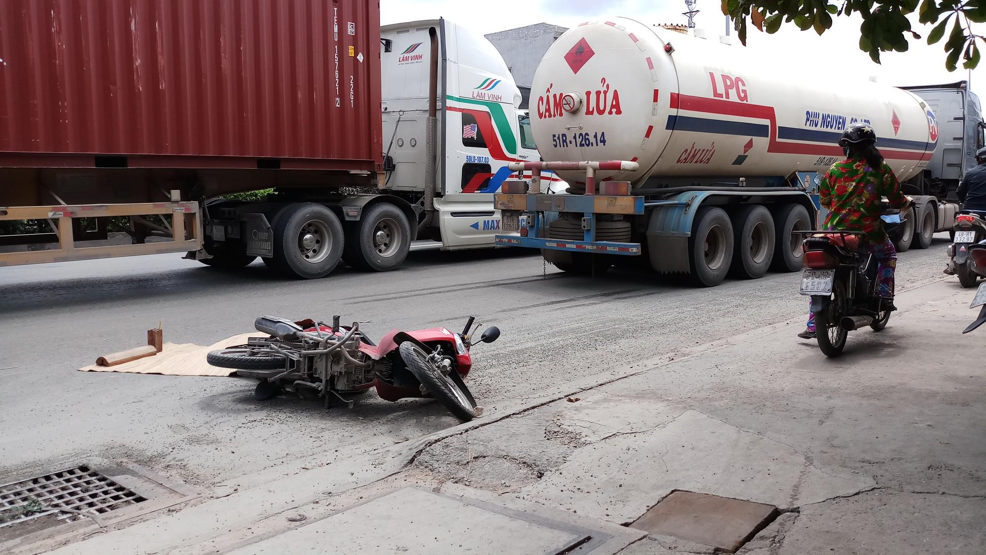 Nạn nhân và chiếc xe máy, xe bồn ở hiện trường.