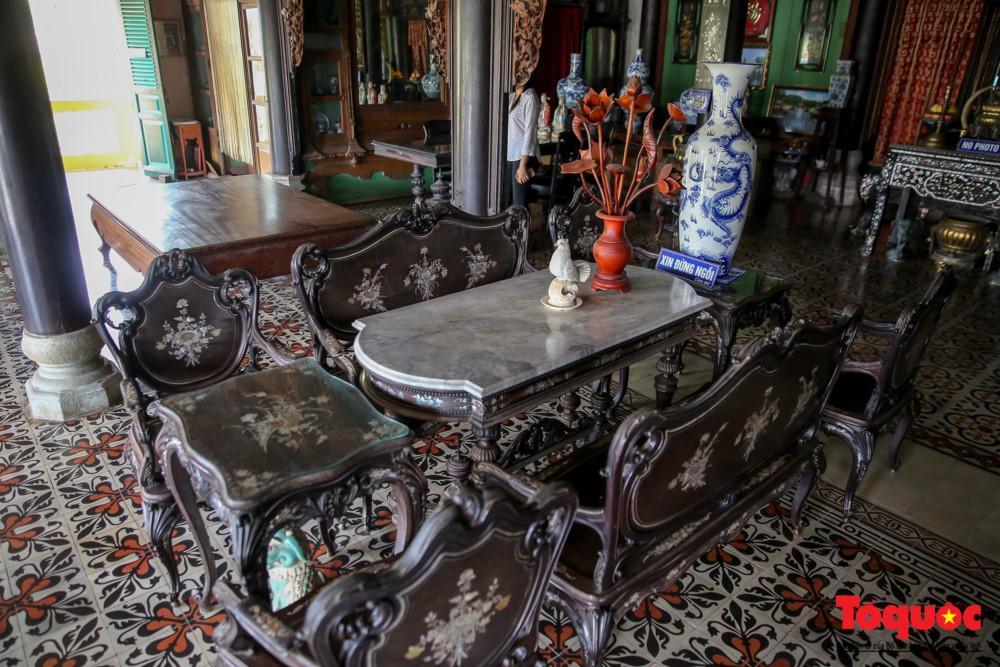 Ngôi nhà nổi bật với ba bộ bàn ghế cổ đẹp và một chiếc sập gụ được trang trí bằng khảm trai tinh xảo cùng những đường nét trạm trổ mềm mại.