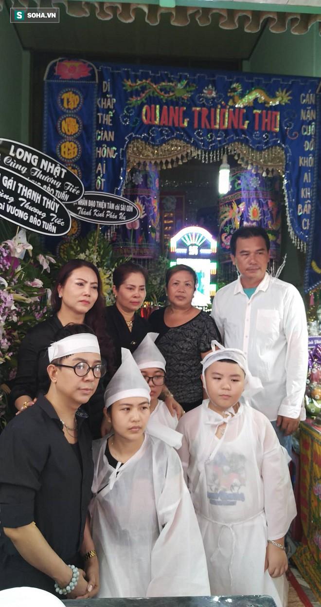 Chị ruột, anh rể, con trai, hai cháu cùng ca sĩ Long Nhật, chị gái kết nghĩa (hàng trên từ trái qua) và chị Phương fan ruột của Vương Bảo Tuấn chụp ảnh kỷ niệm trước linh cữu anh.