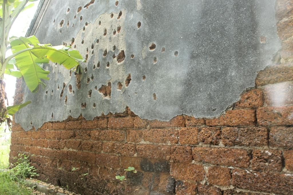 Phía đầu đốc tường đá ong của ngôi đền còn lỗ chỗ dày đặc những vết đạn bắn vào nhưng không thể xuyên thủng được bờ tường