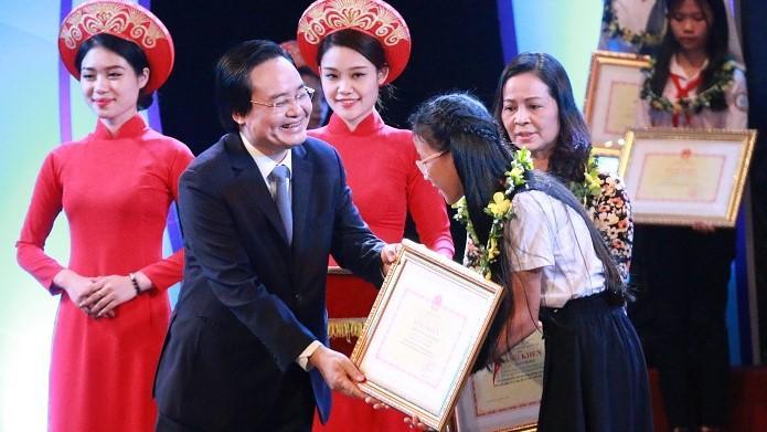 Bộ trưởng Phùng Xuân Nhạ trao bằng khen cho các giáo viên, học sinh tại Lễ tuyên dương gương người tốt, việc tốt đổi mới sáng tạo trong dạy và học năm học 2016-2017. Ảnh: Thanh Hùng.