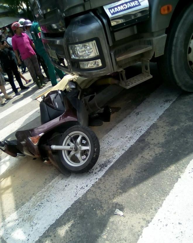 Xe máy bị hư hỏng nặng dưới bánh xe tải.