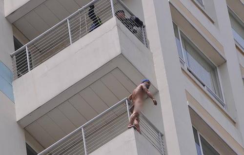 Nam thanh niên khỏa thân đứng ở ban công tầng 10 của bệnh viện. Ảnh: Thái Hà.