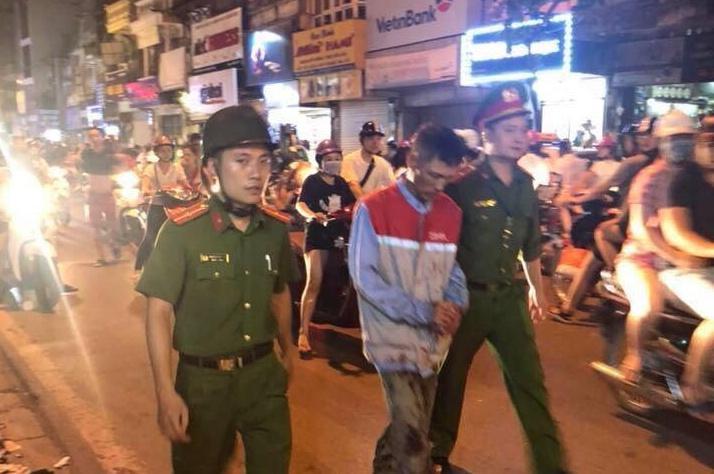 Ông Huấn bị công an bắt giữ sau khi cầm kéo truy sát vợ cũ.