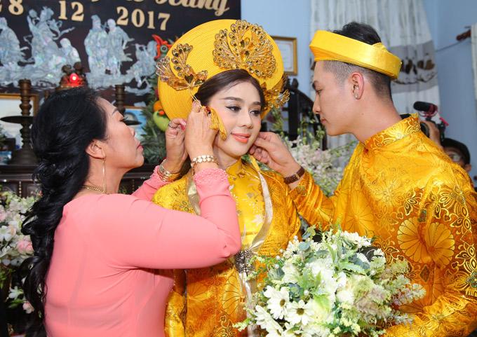 Chú rể và mẹ chồng đeo trang sức cưới cho cô dâu.