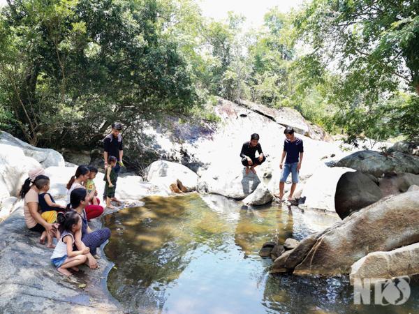 Du khách tham quan và tận hưởng không khí mát mẻ tại suối Gia Nhông.