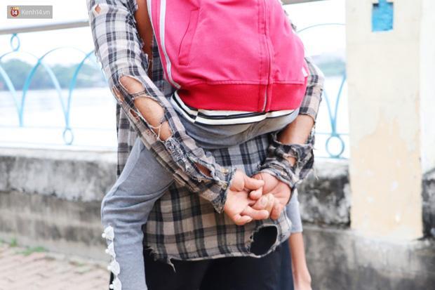 Hình ảnh người cha cõng con gái, phía sau là tấm áo chẳng lành lặn khiến những ai thấy đều xúc động