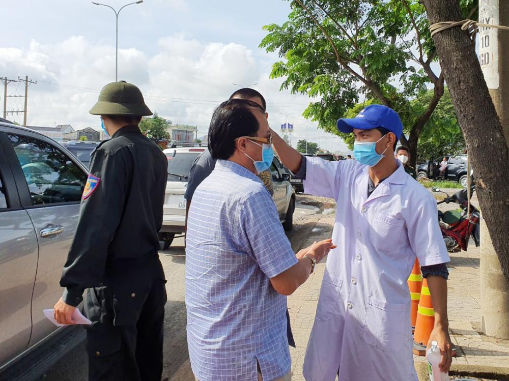 Nhân viên y tế đo thân nhiệt cho người vào BR-VT tại chốt kiểm soát dịch bệnh COVID-19 quốc lộ 51. Ảnh: TUYẾT MAI