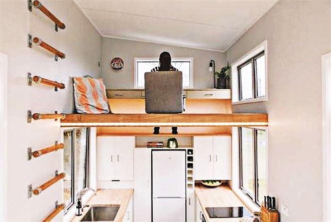 Cầu thang ẩn trong tường có thể kéo ra, vào, dưới là bồn rửa mặt, chỗ nấu ăn.