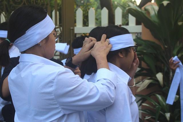 Những vành khăn trắng được các bạn học đeo vội trước giờ làm lễ