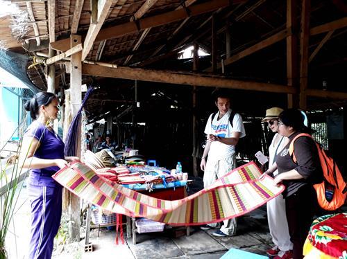 Du khách nước ngoài tìm hiểu về nghề dệt chiếu xã Nhơn Thạnh, thành phố Bến Tre. Ảnh: Trần Thị Thu Hiền - TTXVN